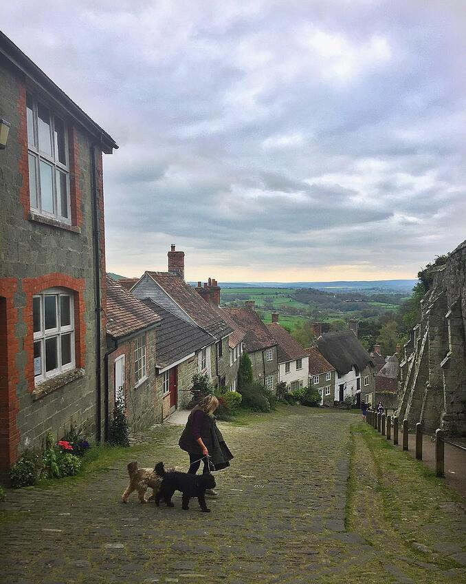 A woman walking two dogs down a cobbled street in Shaftesbury for Fresh Air Friday