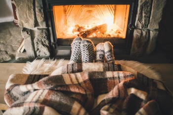 Two people sat in front of a cosy fireplace