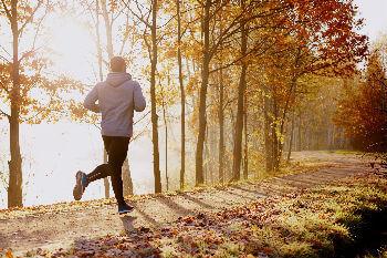 Man running along pathway in autumn