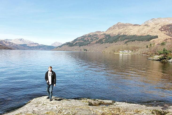 Entire view of Loch Lomond in The Trossachs National Park with a male figure stood by the lake's edge