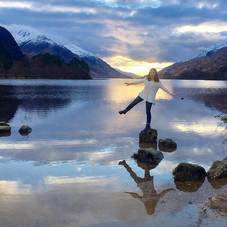 A woman balancing on one leg on a stone in Loch Shiel, Scotland