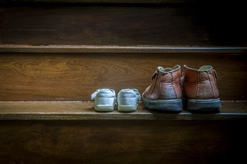 Father and child leave their shoes on the stairs