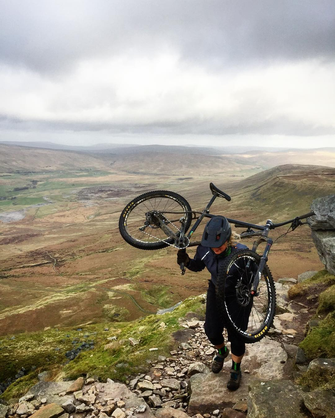 Sam Flanagan carrying a mountain bike to the top of Ingleborough for Fresh Air Friday