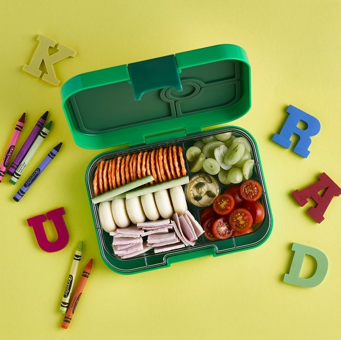 School lunch box with rice crackers, ham, cheese, grapes and tomato