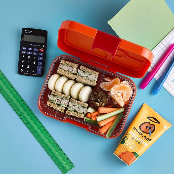 A school lunch box with tuna sandwiches, cheese, oranges and carrot sticks