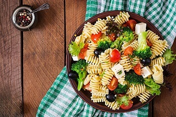 Pasta with broccoli, tomato and olives.