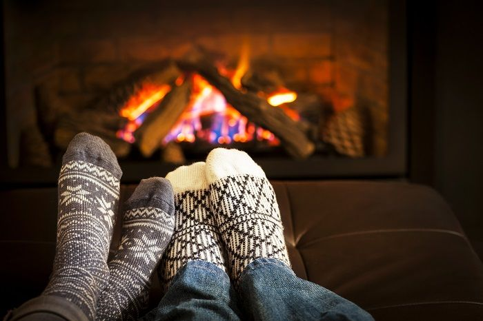Couple cuddling on front of the fire