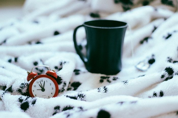 Alarm clock and mug on a blanket