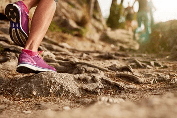Runner with pink trainers on a muddy path