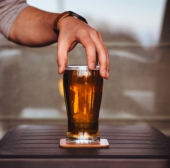 A pint of beer on a table.