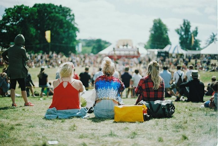 Three women enjoy the sun at a festival