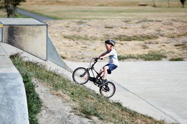 Child riding a bike up a hill.