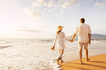 Couple walking along a beach holding hands