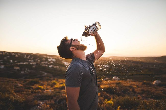 Man staying hydrated on a hot summer's day