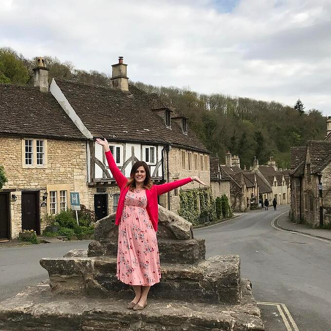 Woman in red dress standing in Castle Combe village for Fresh Air Friday