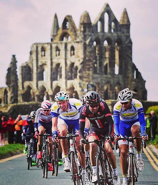 Five cyclists riding along a road for Tour de Yorkshire with Whitby abbey in the background - Fresh Air Friday inspiration.