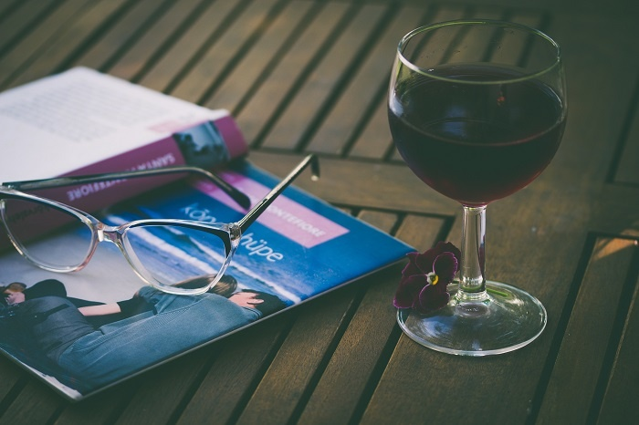 A glass of red wine with a book