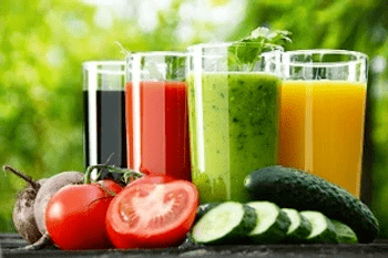 Selection of smoothies behind prepared vegetables