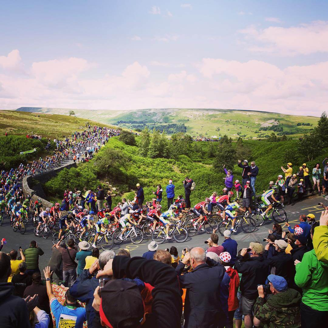 Hundreds of cyclists riding up a hill in the Yorkshire dales, Fresh Air Friday inspiration. Thanks to Tour de Yorkshire on Instagram