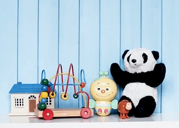 A doll's house, spinning toy, wind-up toy and teddy bear lined up