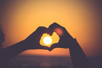 Heart-shaped hands linked over of a sunset