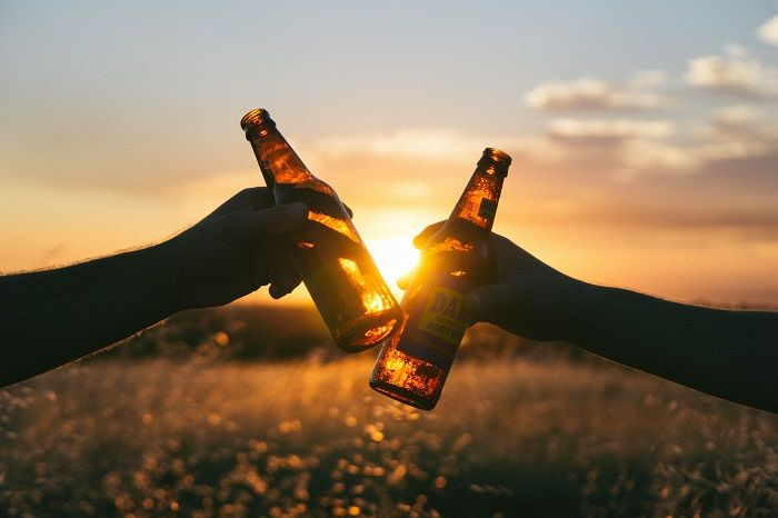 Two friends sharing a beer.