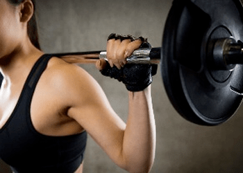 Close-up of young female weightlifter performing a weighted squat