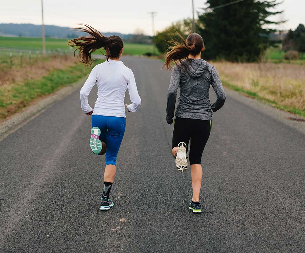 Two women road running