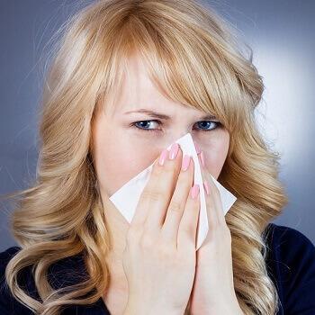 Woman using tissue to catch virus