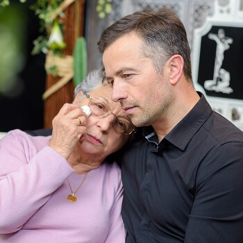 Man comforts grieving woman
