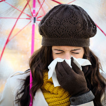 Woman sneezing due to cold