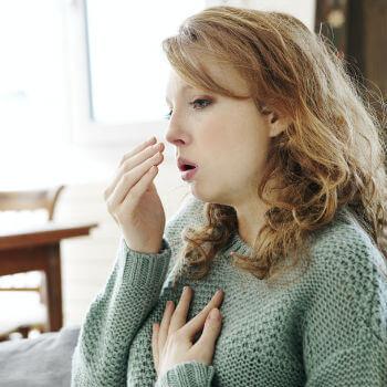 Woman stifling a cough