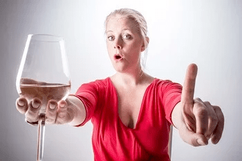 Women holding a glass of wine and pointing accusingly