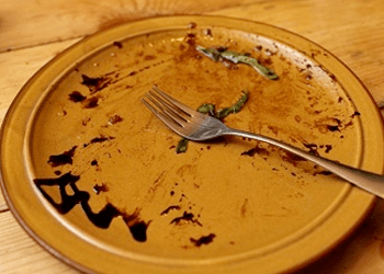 A licked clean plate with chocolate sauce and a fork
