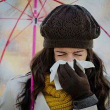 Woman with nasal congestion sheltering from rain