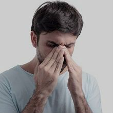 Man with flu touching his nose
