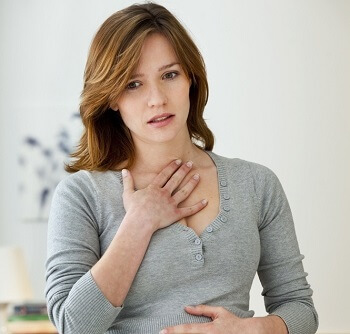 Woman clutching her chest in pain